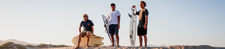three guys with surfboards