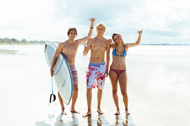 three friends on the beach with surfboard