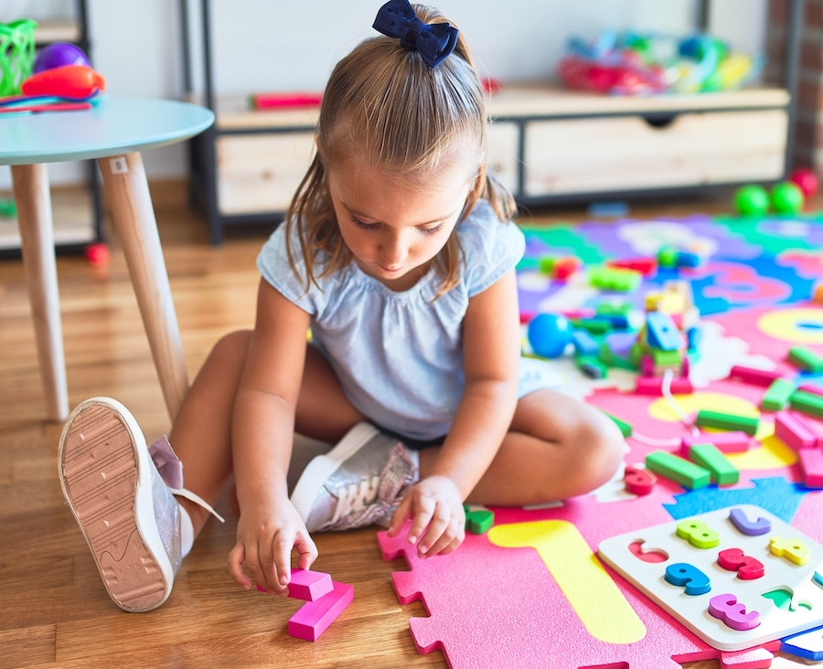Young beautiful blonde girl kid enjoying play school with toys at kindergarten, smiling happy playing at home