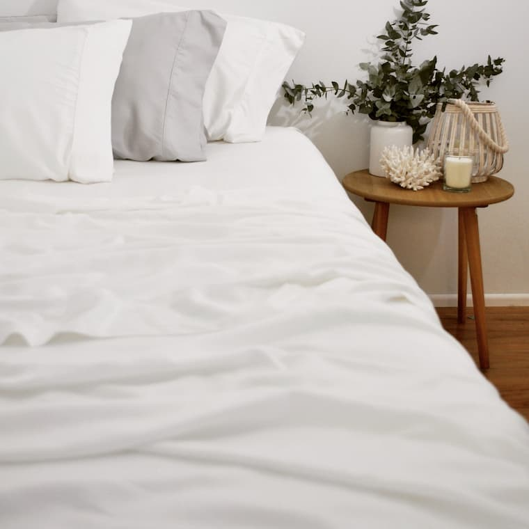 white bamboo sheet set for bedroom with side wood table and decorative candle and flower