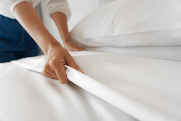 woman's hand on bamboo bedding