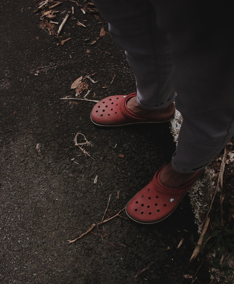 picture of a person wearing red clogs and black trousers, standing on a concrete