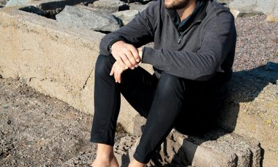 picture of a men witting on rocks near water wearing warm outfit and black clogs